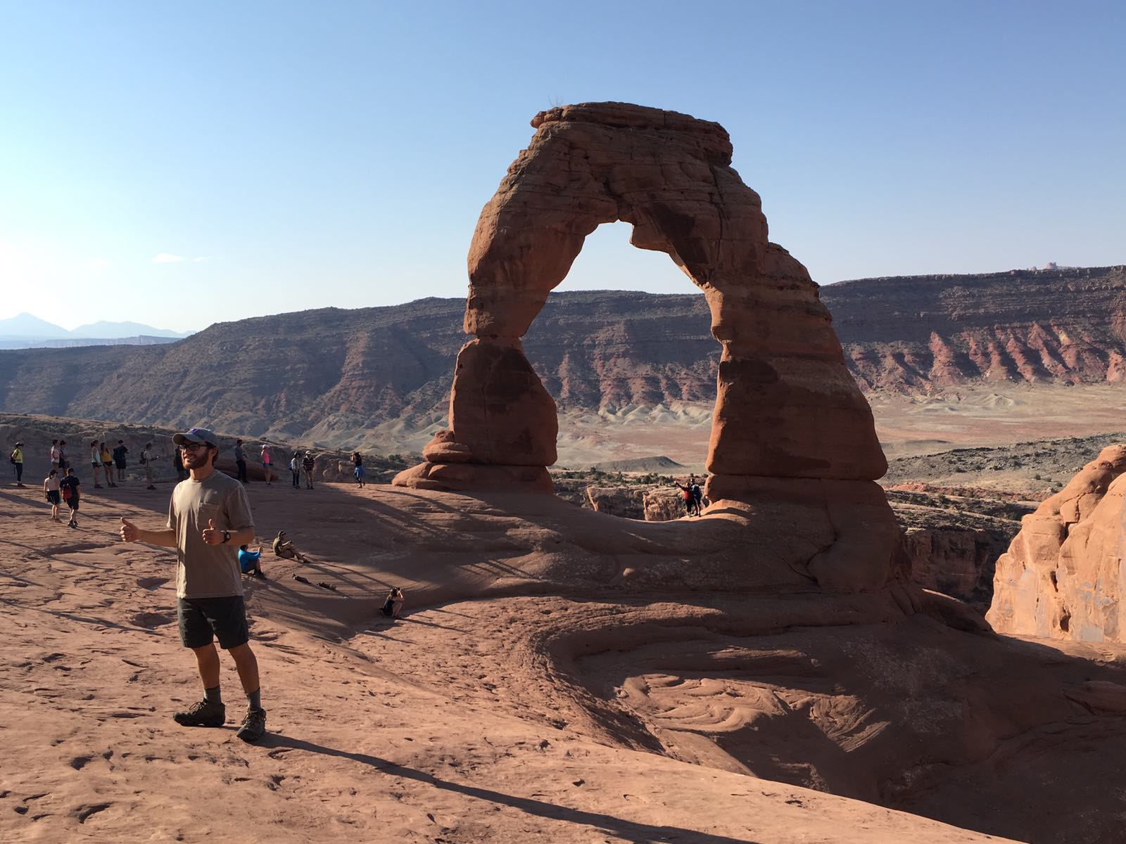 Delicate arch in background, in foreground a young man gives two thumbs up.